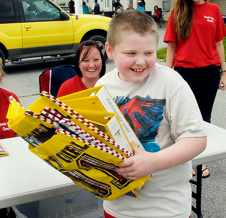 John P. Cleary | The Herald Bulletin<br /> Skylar King, 9, gets a handful of bags and binders for the tokens he won at the games he played at the Greater Light Gives Back event Saturday hosted by Greater Light Church.  Skylar was going to give these prizes away to others who hadn't won anything yet.  To view or buy this photo and other Herald Bulletin photos, visit<br /> photos.heraldbulletin.com.