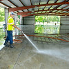 John P. Cleary | The Herald Bulletin<br /> Alexandria Street Department workers hose down the floor of the Kiwanis Building as they prepare for the start of the Madison County 4-H Fair this coming weekend.