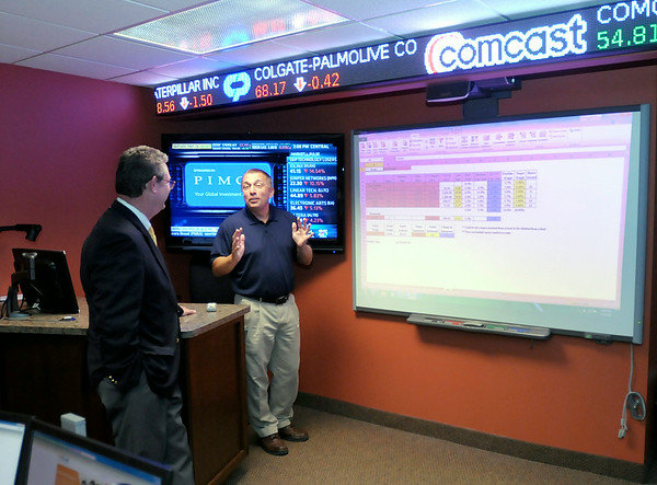 Don Knight | The Herald Bulletin<br /> Finance and economics professor Kent Saunders, right, gives a tour of the Star Trading Room to President of Star Wealth Management Keith Davis on Wednesday. Davis visited Anderson University's Falls School of Business to deliver a $25,000 check, the fifth installment in a $125,000 commitment to fund the Star Trading Room.
