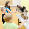 Don Knight | The Herald Bulletin<br /> From top, Madison Baker Mason Baker and Alex Ervin touch a turkey vulture during Investigation Station at the Anderson Public Library on Wednesday. DNR Seasonal Interpretive Naturalist Aaron Douglass talked about birds and kids also built a bird feeder. Investigation Station is for ages 6 to 12 and meets on Monday, Wednesday and Friday from 2 to 3 p.m. in the Cardinal Room.