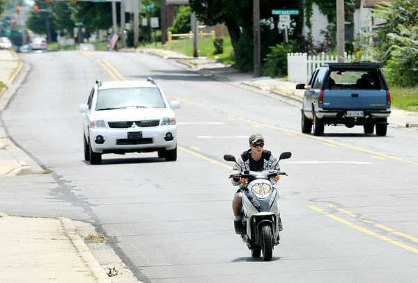 Don Knight | The Herald Bulletin<br /> A scooter travels north on Madison Avenue on Saturday. On Jan. 1, 2015, Indiana will require registration and tagging of all motorized bicycles.