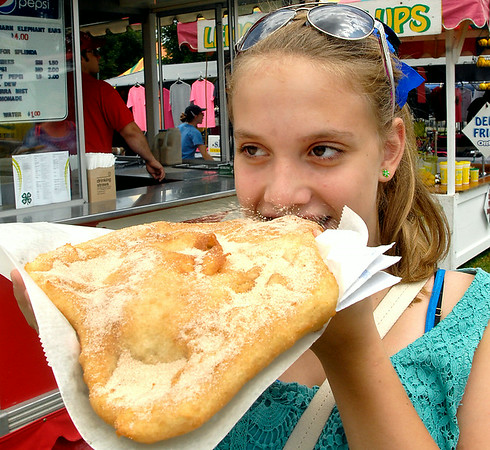 John P. Cleary | The Herald Bulletin<br /> One of the mainstays of fair food is the fried, sweet and doughy Elephant Ear. Here Parker Graham, 12, takes that first big bite of her midway treat at the Madison County 4-H Fair.