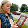 John P. Cleary | The Herald Bulletin<br /> Leann McKissack stands at the intersection of Indiana 236 and Markleville Road holding a photograph of her parents Eugene and Janet Shaw who were killed in a vehicle accident there 50 years ago.