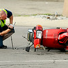 John P. Cleary   The Herald Bulletin<br /> An Anderson Police Department investigator photographs the scene of a serious personal injury accident involving this moped and a car at 29th & Main Streets in Anderson around 6 p.m. Monday evening.