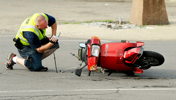 John P. Cleary | The Herald Bulletin<br /> An Anderson Police Department investigator photographs the scene of a serious personal injury accident involving this moped and a car at 29th & Main Streets in Anderson around 6 p.m. Monday evening.