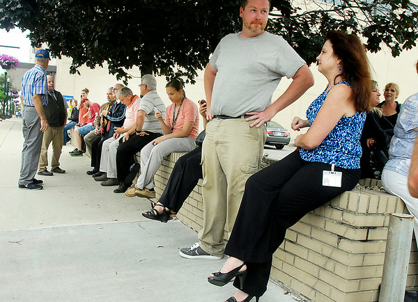 John P. Cleary | The Herald Bulletin<br /> Madison County Government Center employees wait along Meridian Street after being evacuated from the building do to a bomb threat Monday afternoon.