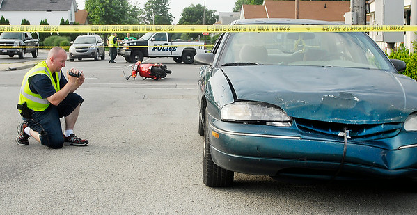 John P. Cleary | The Herald Bulletin<br /> An Anderson Police Department investigator photographs the scene of a serious personal injury accident involving a moped and a car at 29th & Main Streets in Anderson around 6 p.m. Monday evening.