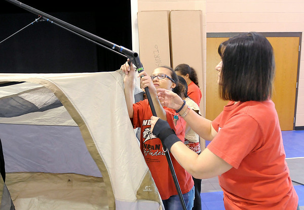 Don Knight | The Herald Bulletin<br /> From left, Melody Scarfullery and Vickie Widing set up a tent at Cross Street Christian School. The tents were being set in the gym to air them out and ensure they have all the parts before the Pathfinders travel to Oshkosh Wisconson.