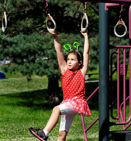 John P. Cleary | The Herald Bulletin<br /> Dani Patton, 7, wearing her favorite hair band, swings to grab the next rung as she plays at Shadyside Lake playground while out with her family enjoying the afternoon.