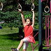 John P. Cleary   The Herald Bulletin<br /> Dani Patton, 7, wearing her favorite hair band, swings to grab the next rung as she plays at Shadyside Lake playground while out with her family enjoying the afternoon.