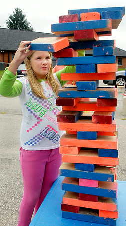 "John P. Cleary | The Herald Bulletin<br /> Khloe Baugher, 9, tries her skills at the oversized ""jenga"" game during the Greater Light Churchs'  Greater Light Gives Back event held Saturday.  Players  won tokens for their efforts and then could trade those in for prizes of school supplies.  To view or buy this photo and other Herald Bulletin photos, visit<br /> photos.heraldbulletin.com."