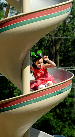 John P. Cleary | The Herald Bulletin<br /> Dani Patton, 7, wearing her favorite hair band, slides down the large spiral slide at Shadyside Lake playground while out with her family enjoying the afternoon.