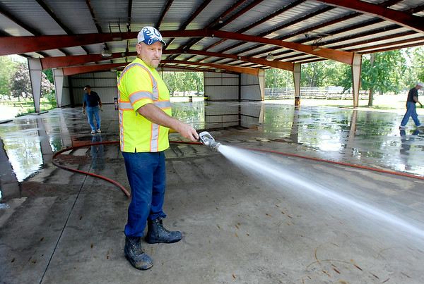 John P. Cleary | The Herald Bulletin<br /> Alexandria Street Department worker Lioniel Martin hoses down the floor of the Kiwanis Building Monday afternoon as preparations for the Madison County 4-H Fair continue for a weekend start to the annual event.
