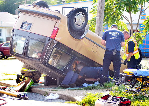John P. Cleary   The Herald Bulletin<br /> Anderson firefighters work to extract the driver of this overturned van after being involved in a two vehicle accident at Cincinnati Ave and Ohio Ave. in Anderson.