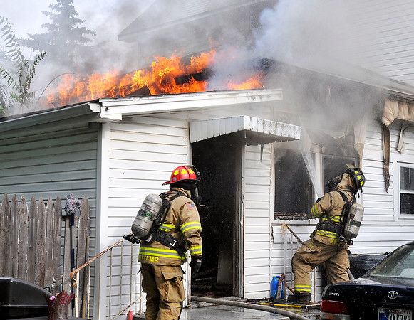 John P. Cleary | The Herald Bulletin<br /> Anderson firefighters battle a house fire at 911 Nichol Ave. Thursday morning that was called in as a kitchen fire. Flames spread through the ceiling to the roof line at the back of the structure. The fire was contained to the kitchen area but the house suffered heavy smoke damage.