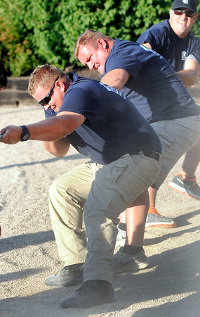 Don Knight   The Herald Bulletin<br /> Anderson Police Department's Community Policing division officer Brett Webb digs in while competing in the tug-of-war event at the Guns and Hoses competition at Hoosier Park earlier this month.