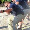 Don Knight | The Herald Bulletin<br /> Anderson Police Department's Community Policing division officer Brett Webb digs in while competing in the tug-of-war event at the Guns and Hoses competition at Hoosier Park earlier this month.