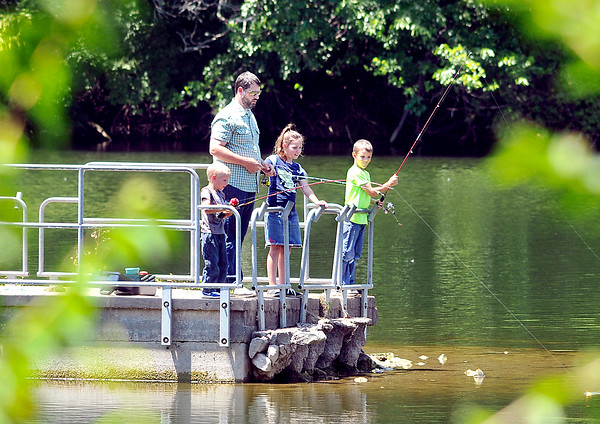 """John P. Cleary   The Herald Bulletin<br /> Ryan Kerr, of Anderson, takes his three children, Isaiah, 4, Savannah, 9, and Austin, 7, to Shadyside Lake Monday afternoon for a little """"family fishing"""" time together."""