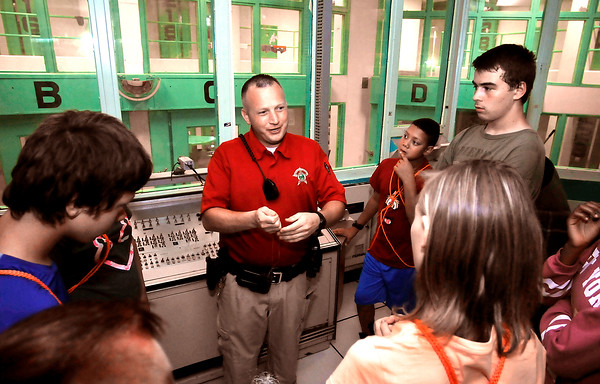 John P. Cleary | The Herald Bulletin<br /> Madison County Sheriff's officer Dustin Jones explains the operations of the county jail from one of the control centers to students in the Indiana State Police Law Camp as they toured the facility Thursday.
