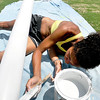 John P. Cleary | The Herald Bulletin<br /> Anderson University senior Victoria Smith puts a primer coat of paint on the south goal post at the Colts practice field Tuesday afternoon in preparation for the start of training camp next week. Smith, who works for the Colts maintenance department, said she will finish up with a bright new coat of yellow paint for the posts.