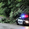 Don Knight | The Herald Bulletin<br /> An APD officer blocks the west bound lane of 18th Street warning motorists of limbs down blocking the road after a thunderstorm moved through Madison County on Wednesday.