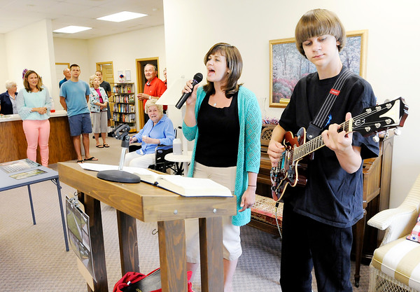 """Don Knight   The Herald Bulletin<br /> Emma Bowen Meyer sings """"I Come to the Garden Alone"""" accompanied on guitar by her son Zeke during the dedication of a new pathway around the retention pond at College Park Condominiums on Saturday."""
