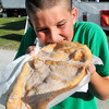 John P. Cleary | The Herald Bulletin<br /> 9 year old Brayden Peters, of Frankton, jumps in to get that first bite of his giant elephant ear at the Madison County 4-H Fair Monday evening.