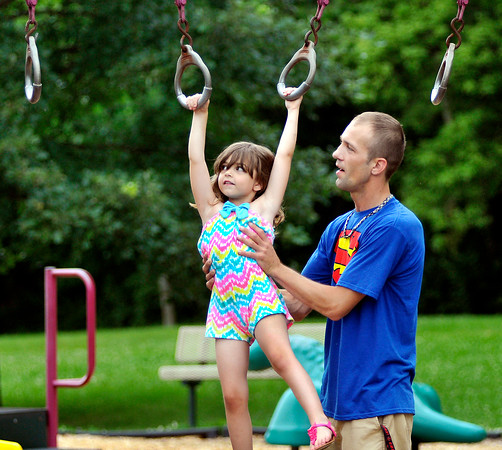 John P. Cleary | The Herald Bulletin<br /> Kyle Thomas, of Anderson, holds up his daughter Hadley, 5, as she works her way along the rings at the Alexandria Pike playground in Shadyside Park Monday afternoon. Thomas was out with his children enjoying an afternoon at the park.