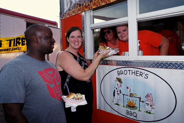 Jason Gibbs and Meagan Mason of Anderson are serve some tasty Brother's BBQ by Kelly Seleyman and Janetta Phipps at Sunday's reescheduled Indepence Day Celebration.