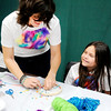 Don Knight | The Herald Bulletin<br /> Christine Erny helps Ava Zdanowski, 8, with her dream catcher during an Anderson Center for the Arts' Girls Art Camp on Thursday.