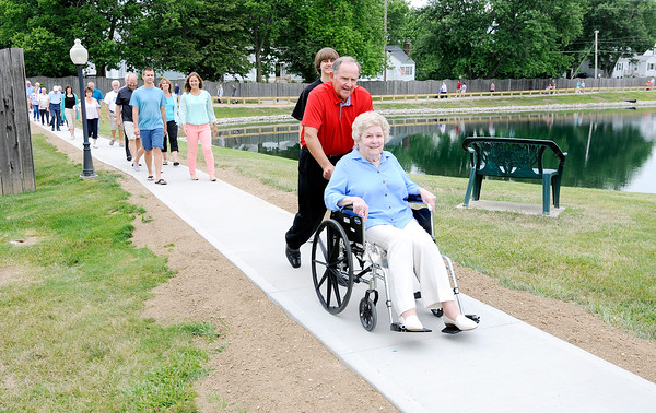 Don Knight   The Herald Bulletin<br /> Carl Bowen pushes his mother Kathy Bowen on a new pathway around the retention pond at College Park Condominiums on Saturday. Kathy provided most of the $18,000 needed to build the pathway.