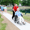 Don Knight | The Herald Bulletin<br /> Carl Bowen pushes his mother Kathy Bowen on a new pathway around the retention pond at College Park Condominiums on Saturday. Kathy provided most of the $18,000 needed to build the pathway.
