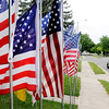 Don Knight | The Herald Bulletin<br /> A car passes a collection of flags on display on 29th Street. Chris Swango and his fiance Fran Hall set out their for the Independence Day holiday.