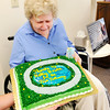 Don Knight | The Herald Bulletin<br /> Kathy Bowen looks at a cake decorated in her honor at a dedication for a new pathway around the retention pond at College Park Condominiums on Saturday.