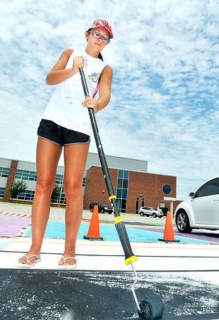 John P. Cleary | The Herald Bulletin<br /> Madison Watters, a senior at Anderson High School, paints her reserved parking space in the high school lot Monday afternoon before school starts next week.  Seniors can pay a $30 fee to have their own parking space in which they can paint it how they like.  The money raised goes toward the AHS senior class fund.