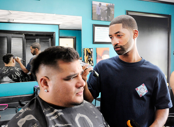 Don Knight | The Herald Bulletin<br /> Jaysson Streaty cuts Shane Butts hair at his new shop, Boonies Barber Shop, on Columbus. The shop is named for Streaty's brother Brandon Boone who was murdered almost two years ago.