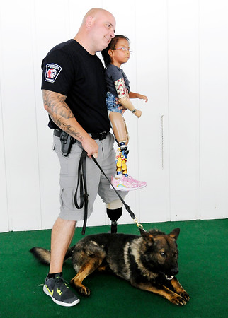 Don Knight | The Herald Bulletin<br /> APD's Marty Dulworth and his K-9 partner Rico pose for a photo with Jennai Gonzalez, 5, during a birthday party for children sponsored by the Madison County Shrine Club on Saturday.