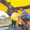 "Don Knight | The Herald Bulletin<br /> Members of the dance group ""Infantry Drill Team"" play in a bounce house during the Edgewood Independence Day Celebration at the Edgewood Country Club on Saturday."