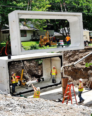John P. Cleary |  The Herald Bulletin<br /> Workers for Culy Contracting maneuver a box culvert section into position as they started to construct the culvert Monday located in the 1400 block of Alexandria Pike. The project, which was originally to be finished June 27th, has been delayed due to water issues caused by the heavy rains and is now targeted for a mid-August completion date. Alexandria Pike has been closed from Lindberg Road to Cross Street since June 6th due to the project.