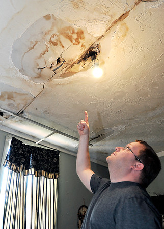 John P. Cleary |  The Herald Bulletin<br /> Sammie Blevins points out the areas of water damage from holes in the roof of his grandmother's house on Church Street in Alexandria where Beverly Master as apparently been scammed out of money and roofing materials by a contractor hired to fix the roof.