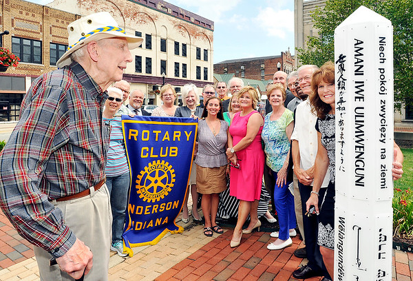 John P. Cleary    The Herald Bulletin<br /> Rotary members celebrate their 100th anniversary around the Peace Pole in Dickmann Town Center Wednesday. Heading up the group is Bob Shoemaker, front left, who is the oldest living member of the Anderson club. Shoemaker, 95, joined the Rotary Club in 1948.