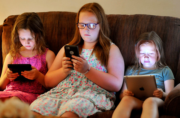 John P. Cleary    The Herald Bulletin<br /> Kira Smith's daughters, Jenna Thacker, 9, Kayla Porter, 11, and Katy Porter, 6, are all involved in using their electronic devices.