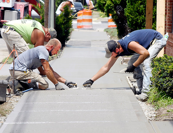 John P. Cleary |  The Herald Bulletin Chris Weaver and Brian Dubuque, of Campbell Brothers Concrete, work from each side as they trowel out the fresh concrete of this new sidewalk along the 800 block of Central Avenue Wednesday.