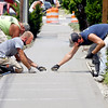 John P. Cleary |  The Herald Bulletin<br /> Chris Weaver and Brian Dubuque, of Campbell Brothers Concrete, work from each side as they trowel out the fresh concrete of this new sidewalk along the 800 block of Central Avenue Wednesday.