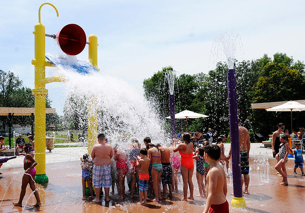 Don Knight   The Herald Bulletin<br /> Kids huddle under a bucket as it dumps water onto them Daleville's new Town Hall Park on Wednesday. The park was full on Wednesday bringing in visitors from across the area.