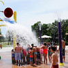 Don Knight | The Herald Bulletin<br /> Kids huddle under a bucket as it dumps water onto them Daleville's new Town Hall Park on Wednesday. The park was full on Wednesday bringing in visitors from across the area.