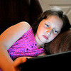John P. Cleary |  The Herald Bulletin<br /> Jenna Thacker, 9, lays on the couch as she uses her tablet.