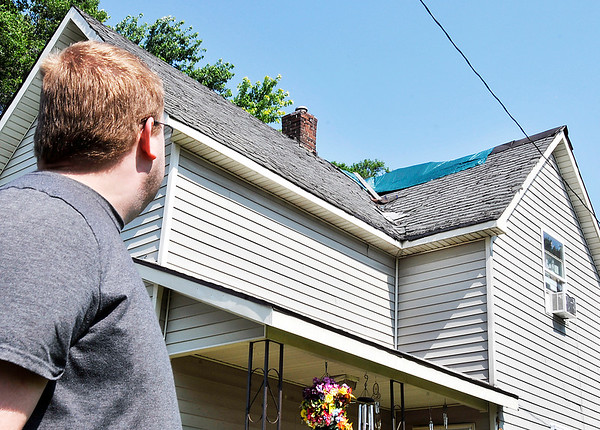 John P. Cleary |  The Herald Bulletin<br /> Sammie Blevins looks over the tarped area of the roof covering up holes of his grandmother's house on Church Street in Alexandria where Beverly Master as apparently been scammed out of money and roofing materials by a contractor hired to fix the roof.
