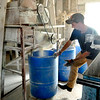 John P. Cleary |  The Herald Bulletin<br /> Anthony Thompson puts another barrel under the grinder as they grind up corn in the feed mill Friday.