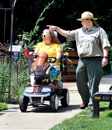 John P. Cleary    The Herald Bulletin<br /> Kelley Morgan, Mounds State Park Interpretive Naturalist, points out things to Kim Ousley who's riding the new scooter the park has that the Friends of Mounds Park had donated to the park for people with disabilities to get around the park easier.